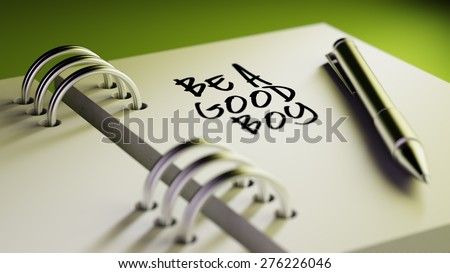 Closeup of a personal agenda setting an important date writing with pen. The words Be a good boy written on a white notebook to remind you an important appointment.