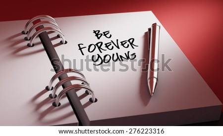 Closeup of a personal agenda setting an important date writing with pen. The words Be Forever young written on a white notebook to remind you an important appointment. - stock photo