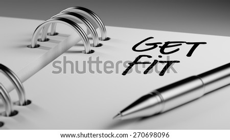 Closeup of a personal agenda setting an important date writing with pen. The words Get Fit! written on a white notebook to remind you an important appointment.