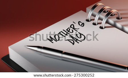 Closeup of a personal agenda setting an important date writing with pen. The words Mother's Day written on a white notebook to remind you an important appointment.