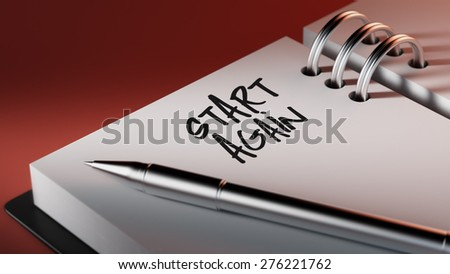 Closeup of a personal agenda setting an important date writing with pen. The words Start Again written on a white notebook to remind you an important appointment.