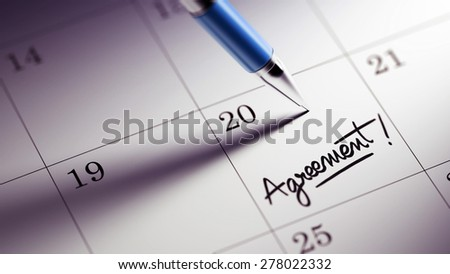 Closeup of a personal agenda setting an important date written with pen. The words Agreement written on a white notebook to remind you an important appointment.