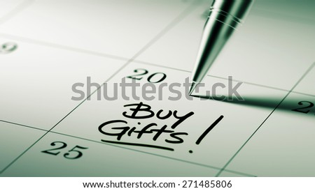 Closeup of a personal agenda setting an important date written with pen. The words Buy Gifts written on a white notebook to remind you an important appointment.