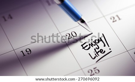 Closeup of a personal agenda setting an important date written with pen. The words Enjoy Life written on a white notebook to remind you an important appointment.