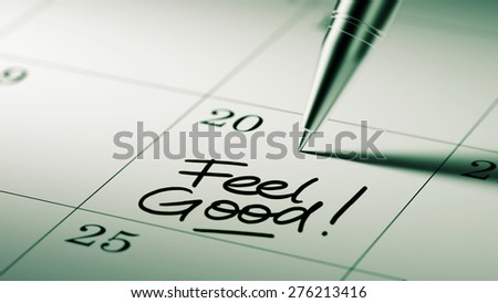 Closeup of a personal agenda setting an important date written with pen. The words Feel Good written on a white notebook to remind you an important appointment.