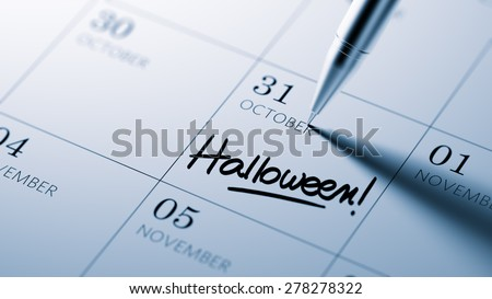 Closeup of a personal agenda setting an important date written with pen. The words Halloween written on a white notebook to remind you an important appointment.
