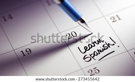 Closeup of a personal agenda setting an important date written with pen. The words Learn Spanish written on a white notebook to remind you an important appointment.
