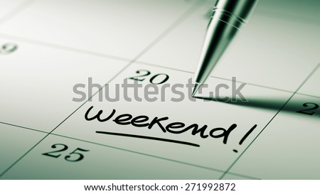 Closeup of a personal agenda setting an important date written with pen. The words Weekend written on a white notebook to remind you an important appointment.