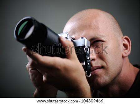 Closeup of a photographer with camera - stock photo