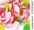 closeup of a pile of candy canes, gumdrops and marshmallows - stock photo