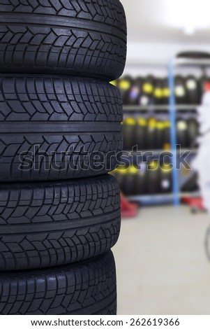 Closeup of a pile of four black tires in the spare parts store - stock photo