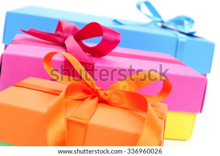 closeup of a pile of gift boxes of different sizes and colors tied with satin ribbon on a white background - stock photo