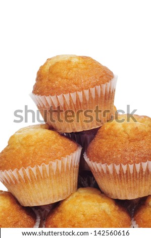 closeup of a pile of plain muffins on a white background - stock photo