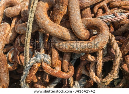 Closeup of a pile of thick rusted chains and ropes of a ship in sunlight on the bank of an estuary. - stock photo
