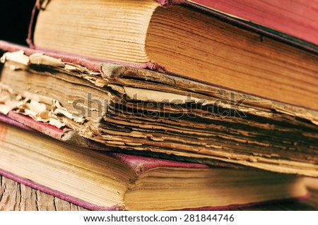 closeup of a pile of worn-out old books on a rustic wooden table - stock photo