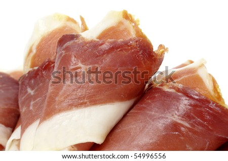closeup of a pile rolled slices of spanish serrano ham