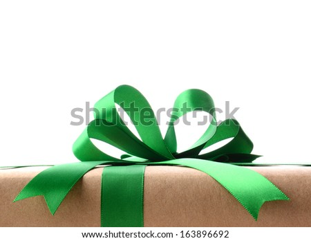 Closeup of a plain wrapped Christmas gift with green ribbon and bow. Only the top portion of the present is shown against a white background. Horizontal format. - stock photo