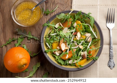 Closeup of a plate of arugula salad with mandarins, oranges, beans sprouts, and sliced almonds served with mandarin vinaigrette for healthy lunch.