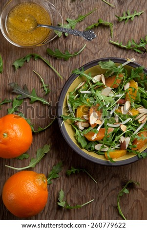 Closeup of a plate of arugula salad with mandarins, oranges, beans sprouts, and sliced almonds served with mandarin vinaigrette for healthy lunch. - stock photo