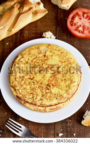 closeup of a plate with a typical tortilla de patatas, a spanish omelet, on a dark wooden table