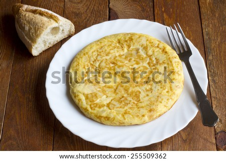 "Closeup of a plate with a typical ""tortilla de patatas"", ""spanish omelet"", on a set table"
