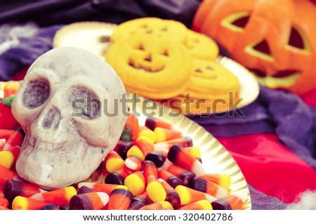 closeup of a plate with Halloween candies and a skull, and some pumpkin-shaped cookies with scary ornaments in the background, such as a jack-o-lantern - stock photo