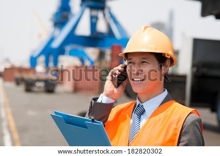 Closeup of a port engineer making a business call at a seaport - stock photo