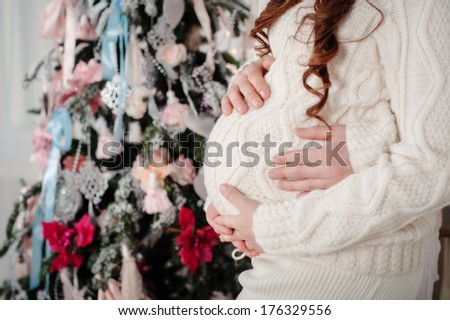 closeup of a pregnant woman's belly embraced by arms against christmas tree - stock photo