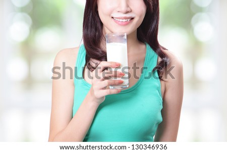 Closeup of a pretty young woman holding a glass of fresh milk isolated on green background, asian beauty - stock photo