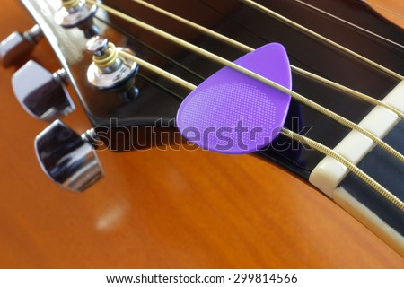 Closeup of a purple pick on metallic chord in acoustic guitar head stock - stock photo
