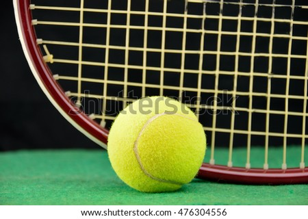 closeup of a racquet and tennis ball at a tennis green court