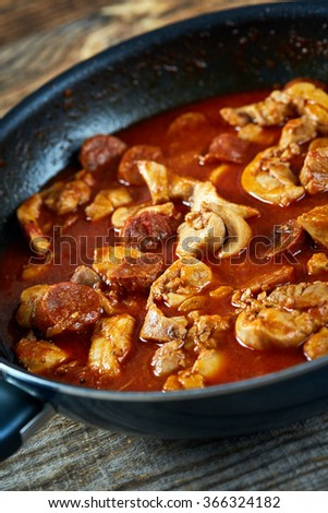 Closeup of a recipe with chicken meat and chorizo sausages in the frying pan