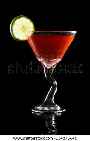 closeup of a red cocktail garnished with a lime wheel isolated on a dark background - stock photo