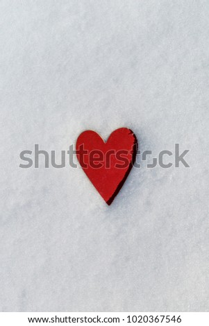 closeup of a red heart on the snow, with some blank space around it