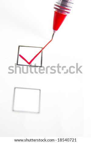 closeup of a red pen checking a box - stock photo