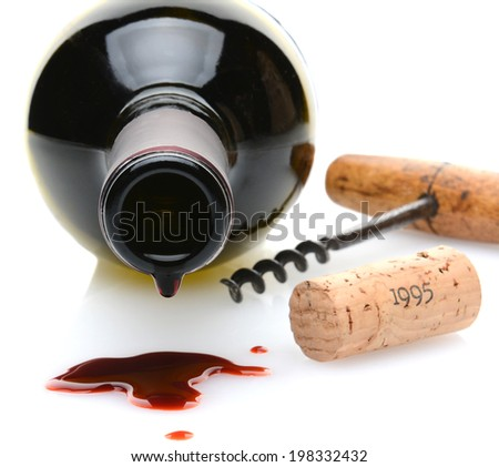 Closeup of a red wine bottle with a drip and wine spill in the foreground. A cork screw and cork to one side on a white background with slight reflection. Shallow depth of field with focus on the drip - stock photo