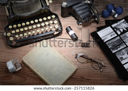Closeup of a retro photography still life with typewriter, folding camera, loupe, roll film, flash bulbs, contact prints and book on a wood table. Black and white toned image for a vintage feel.  - stock photo