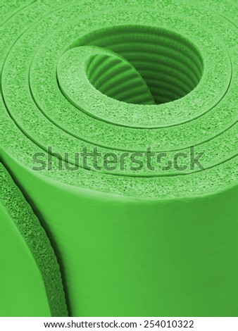 Closeup of a rolled up green exercise mat - stock photo