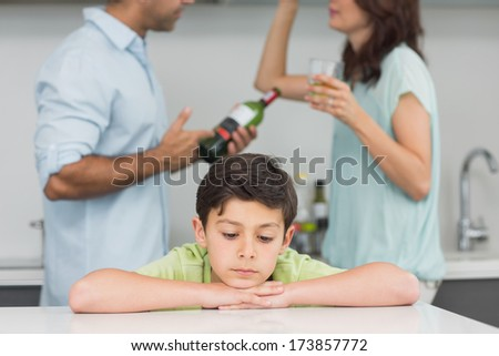 Closeup of a sad son while parents quarreling in the kitchen - stock photo