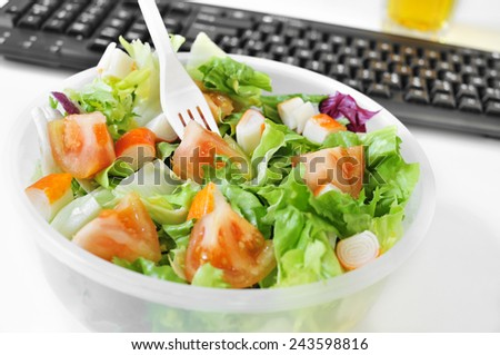 closeup of a salad in a plastic container on the desk of an office - stock photo