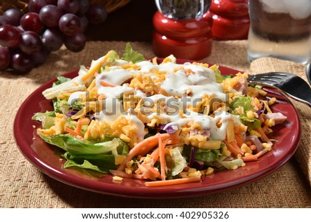 Closeup of a salad with ham, turkey, carrots, cheddar cheese and ranch dressing - stock photo