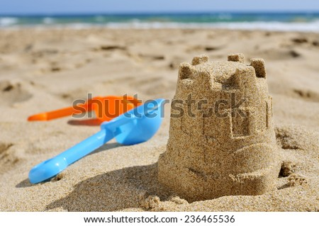 closeup of a sandcastle and toy shovels of different colors on the sand of a beach - stock photo