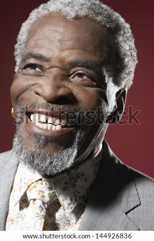 Closeup of a senior African American man smiling against red background - stock photo