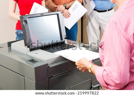 Closeup of a senior woman casting her ballot on a new electronic voting machine.   - stock photo