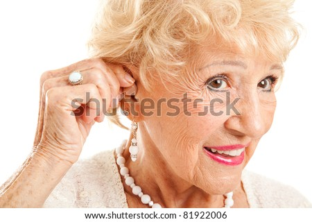Closeup of a senior woman inserting a hearing aid in her hear.  Focus on the hearing aid.