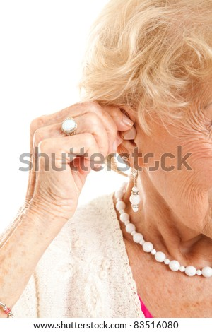 Closeup of a senior woman's hand inserting a hearing aid in her hear. - stock photo