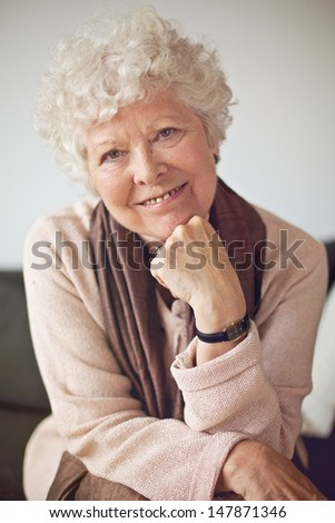 Closeup of a senior woman sitting at home and looking at the camera - stock photo
