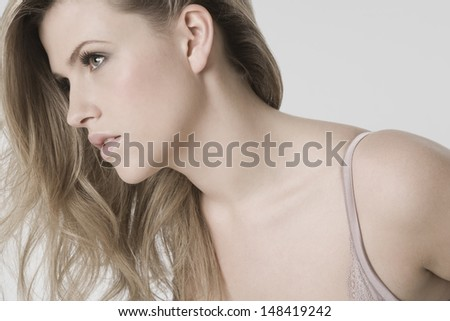 Closeup of a sexy young woman looking away against gray background - stock photo