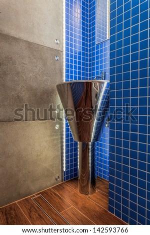 Closeup of a silver modern washbasin in a bathroom - stock photo