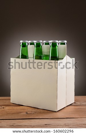 Closeup of a six pack of green beer bottles on a rustic wooden table. Vertical format with a light to dark gray spot background.